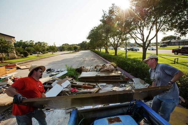 Colbin Holtz, left, and Steven Hanks, right, throw out damaged furniture, doorways and items as volunteers clean up First United Methodist Church in Dickinson earlier this month to prepare for Sunday services. Hauling away  the debris could take months, city officials say.