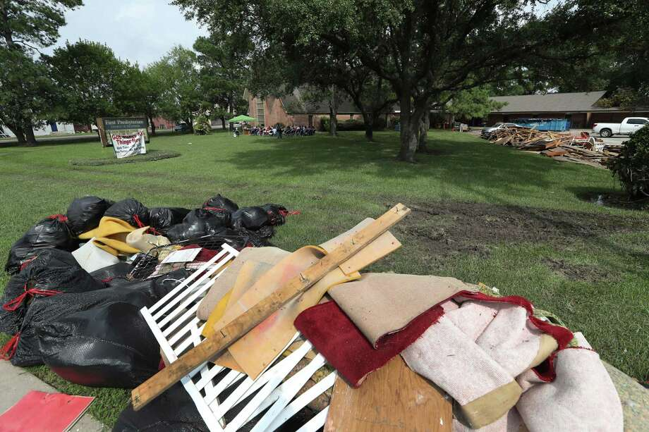 Debris lines the property of The First Presbyterian Church of Dickinson while a outside worship service was held on the front lawn Sunday, Sept. 3 in Dickinson. First Presbyterian Church of Dickinson was badly damaged in the floods from Hurricane Harvey, with only the stained glass left undamaged. Photo: Steve Gonzales, Staff / © 2017 Houston Chronicle