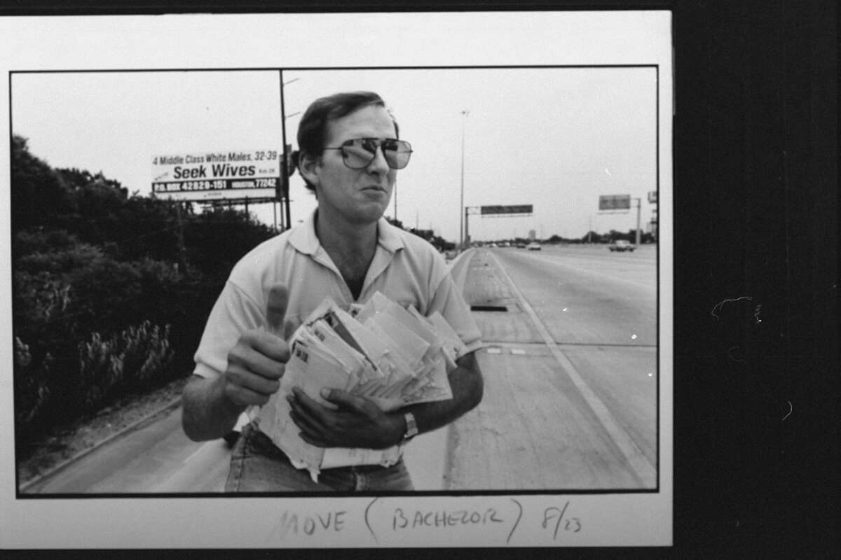 """In 1993, research technician Bill Machmer, 40, divorced since 1990, holds a handful of letters as he stands in front of roadside billboard. The billboard is emblazoned with the text """"4 MIDDLE CLASS WHITE MALES, 32-39, SEEK WIVES, KIDS OK, WRITE PO BOX 42829-151 HOUSTON"""" for which Machmer and three other men each paid $2,500 per month."""