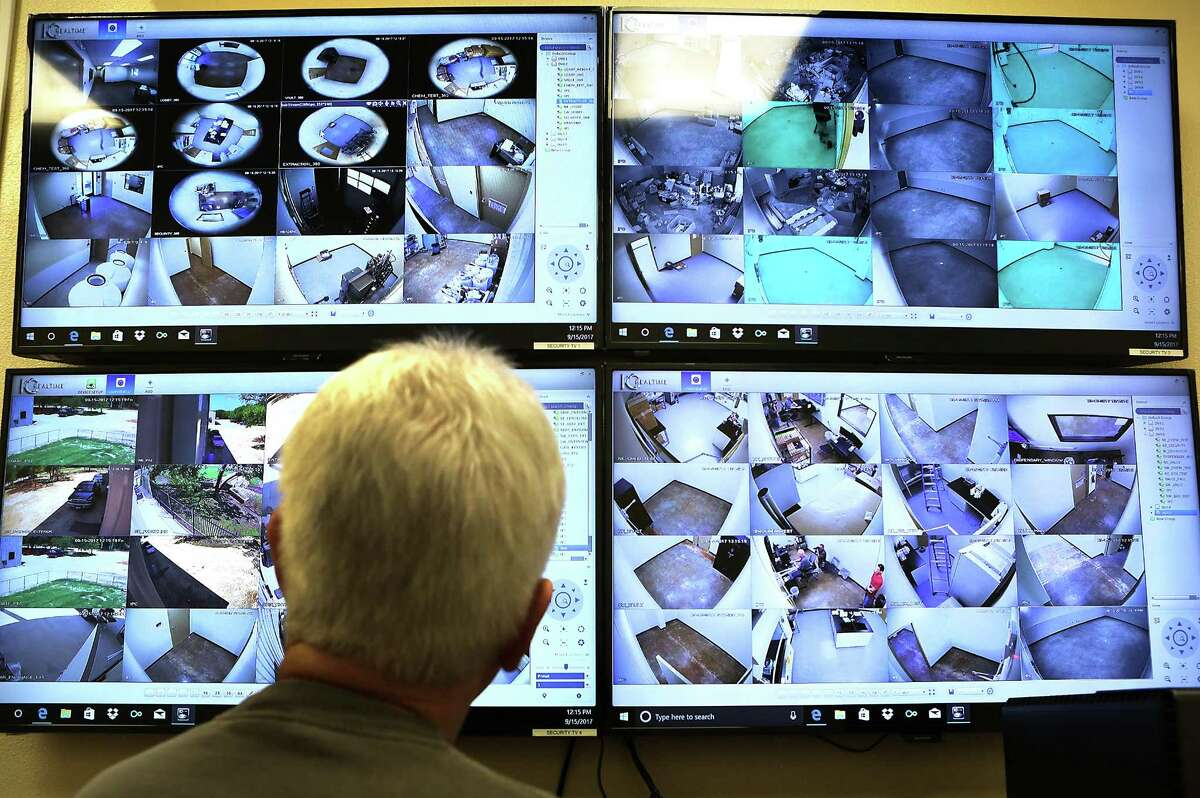 An employee at Compassionate Cultivation, monitors video cameras in the security room at the company that is expected to soon get a license to grow medical cannabis in South Austin.