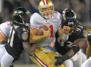 San Francisco 49ers quarterback Alex Smith is sandwiched by Baltimore Ravens cornerback Lardarius Webb (21), and defensive end Cory Redding (93) in the second half of their game on Thursday, November 24, 2011, in Baltimore, Maryland. The Ravens come away with a 16-6 win over the 49ers.