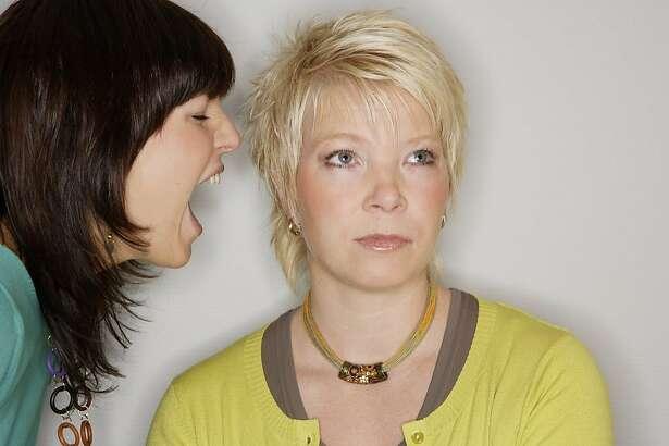 Woman yelling into deaf friend's ear
