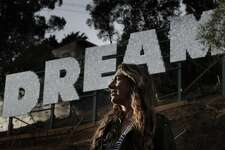 "Ana Teresa Fern�ndez near her huge new work of public art which spells out ""DREAM"" in 12-foot shimmering letters on the east facing slope of Bernal Hill along Highway 101 in San Francisco, Calif., on Monday, September 18, 2017."