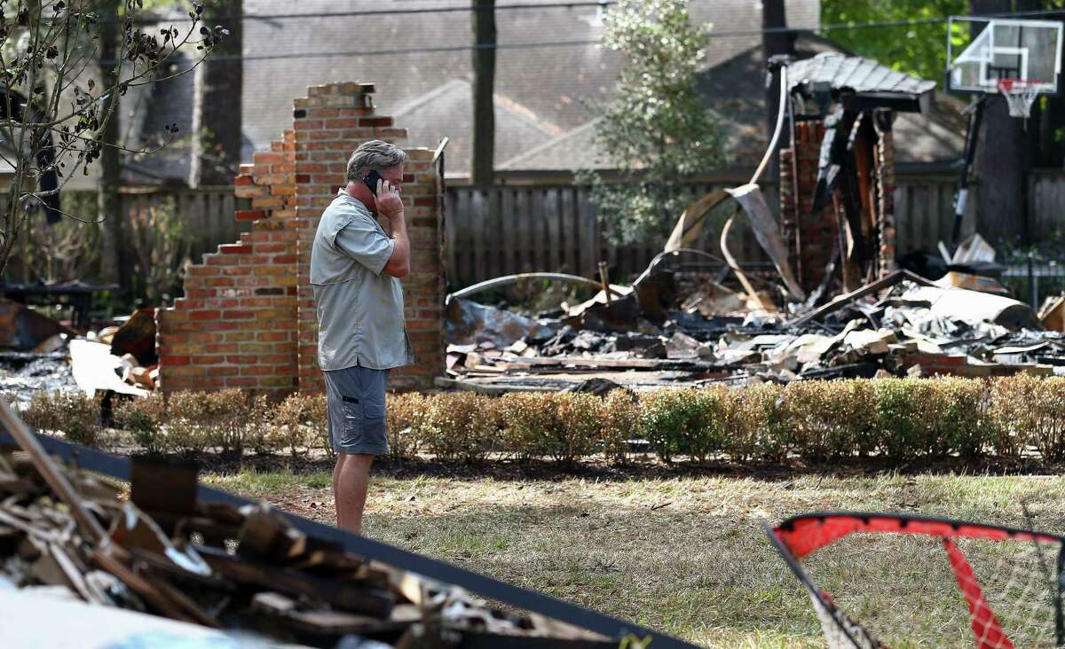 Robert Hooper speaks on the phone while pacing back and forth in front of his burned home on the 13000 block of Boheme Drive Tuesday in Houston. Hooper's home caught fire Tuesday morning, after it had flooded during Hurricane Harvey.