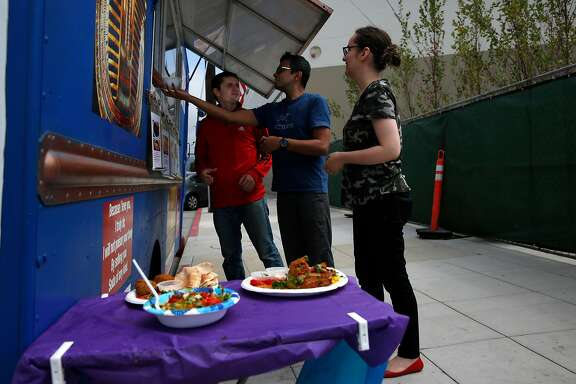 From left, Diogo Martini, Karthick Ramachandran, and Ana Lovejoy receive their food orders at Kader's Royal Egyptian Food Truck Sept. 6, 2017 in Berkeley, Calif.