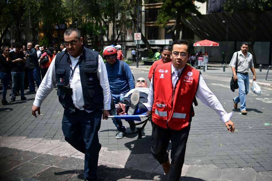 A man is assisted in Mexico City after a real quake rattled the country on September 19, 2017 as an earthquake drill was being held in the capital.