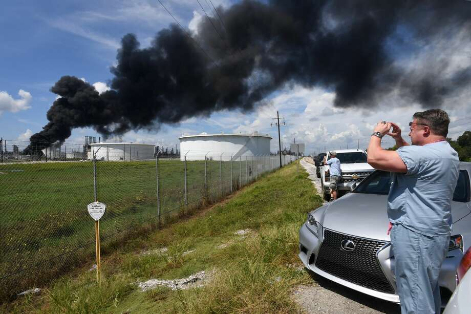 Black smoke rises from a storage tanker at the Valero facility in Port Arthur, Texas on Friday. Several onlookers stop to photograph the site. Photo taken Wednesday, September 19, 20187 Guiseppe Barranco/The Enterprise Photo: Guiseppe Barranco