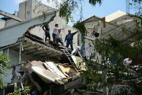 People stand at a building which collapsed after a quake rattled Mexico City on September 19, 2017. A powerful earthquake shook Mexico City on Tuesday, causing panic among the megalopolis' 20 million inhabitants on the 32nd anniversary of a devastating 1985 quake. The US Geological Survey put the quake's magnitude at 7.1 while Mexico's Seismological Institute said it measured 6.8 on its scale. The institute said the quake's epicenter was seven kilometers west of Chiautla de Tapia, in the neighboring state of Puebla.
