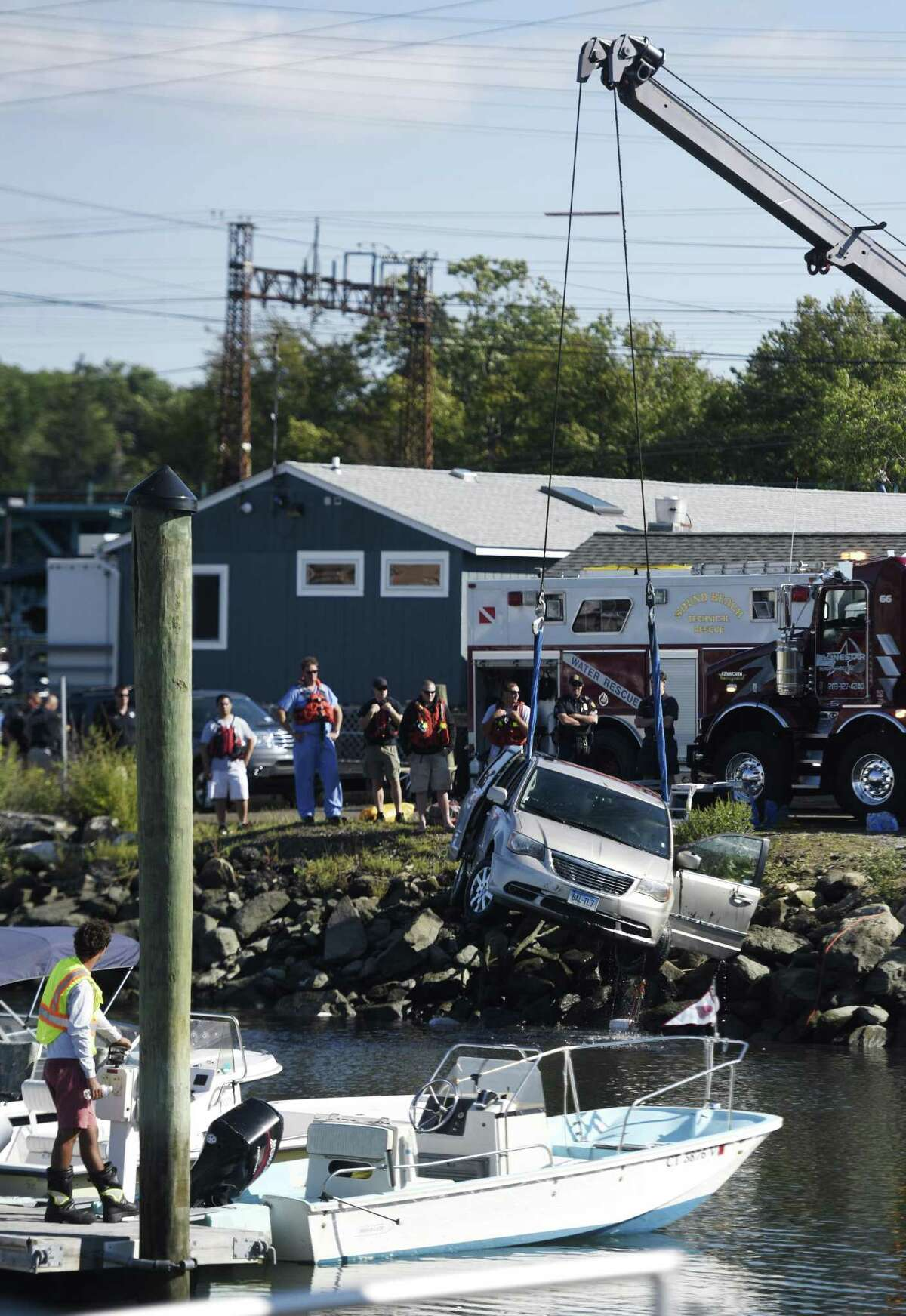 Crews pull a capsized vehicle from Cos Cob Marina in the Cos Cob section of Greenwich, Conn. Monday, Sept. 14, 2015. A New York man in his 80s died after his car fell into the harbor at the marina. Greenwich EMS, fire and police were called to attempt a water rescue, but the man was prounced dead at the scene.
