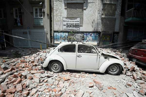 Picture of a car crashed by debris from a damaged building after a quake rattled Mexico City on September 19, 2017. A powerful earthquake shook Mexico City on Tuesday, causing panic among the megalopolis' 20 million inhabitants on the 32nd anniversary of a devastating 1985 quake. The US Geological Survey put the quake's magnitude at 7.1 while Mexico's Seismological Institute said it measured 6.8 on its scale. The institute said the quake's epicenter was seven kilometers west of Chiautla de Tapia, in the neighboring state of Puebla.  / AFP PHOTO / Alfredo ESTRELLAALFREDO ESTRELLA/AFP/Getty Images