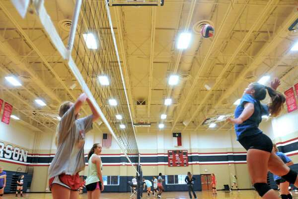 Hardin-Jefferson's Kassidy Shackleford, right, jumps to spike the ball toward teammate Abby Swope, left, during practice Monday at the school's competition gym in Sour Lake. (Mike Tobias/The Enterprise)