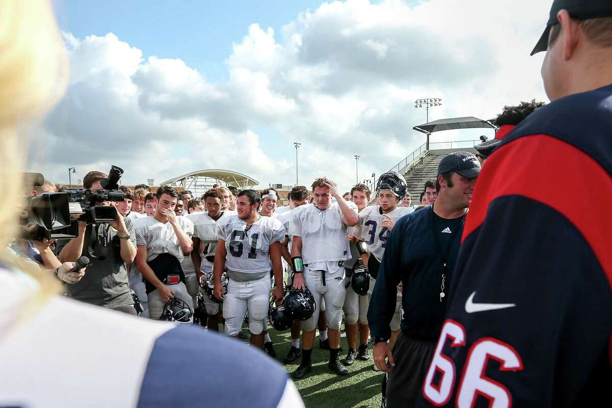 Members of the Kingwood High School varsity football team react as Houston Texans center Nick Martin (66), left, and nosetackle D. J. Reader (98), not pictured, greet them, along with two cheerleaders, to pass out new footballs and shoes, at Turner Stadium, Tuesday, Sept. 19, 2017, in Humble.