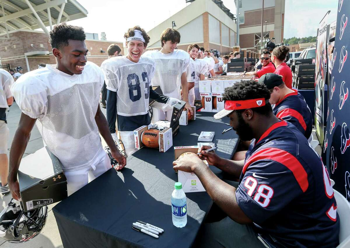 Kingwood High School football players Darrell Edwards, left, and Alex Grifaldo, second from left, joke with Houston Texans nosetackle D. J. Reader (98) as he and center Nick Martin (66) pass out new footballs and shoes, at Turner Stadium, Tuesday, Sept. 19, 2017, in Humble.