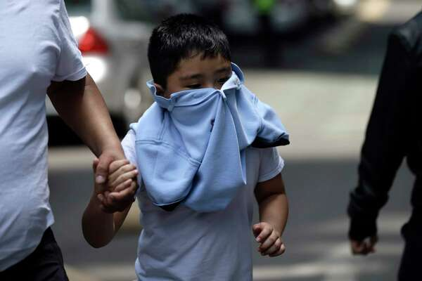 A boy with his face covered due to a gas leak holds aman's hand as people gather in Reforma Avenue after an earthquake in Mexico City, Tuesday Sept. 19, 2017. A powerful earthquake jolted central Mexico on Tuesday, causing buildings to sway sickeningly in the capital on the anniversary of a 1985 quake that did major damage.
