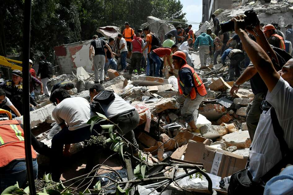 People remove debris of a building which collapsed after a quake rattled Mexico City on September 19, 2017. A powerful earthquake shook Mexico City on Tuesday, causing panic among the megalopolis' 20 million inhabitants on the 32nd anniversary of a devastating 1985 quake. The US Geological Survey put the quake's magnitude at 7.1 while Mexico's Seismological Institute said it measured 6.8 on its scale. The institute said the quake's epicenter was seven kilometers west of Chiautla de Tapia, in the neighboring state of Puebla.