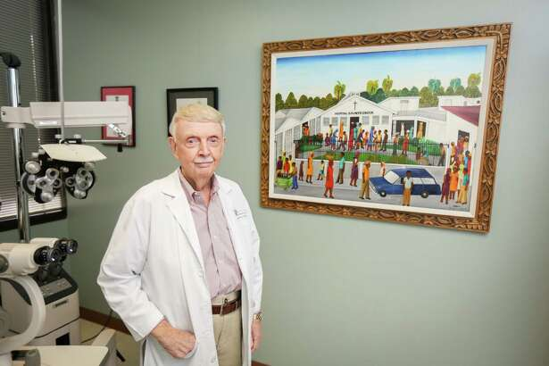 Dr. C. Downey Price, an ophthalmologist with Houston Eye Associates in Conroe, poses for a portrait next to a painting in one of his exam rooms on Monday, Sept. 18, 2017, at his office. The painting was done by Jean Dubic, a Haitian artist. Price befriended Dubic on his many mission trips to Haiti. Dubic eventually became mayor of his hometown of Leogane, Haiti. However, because Dubic was educated this was seen as a threat to those in power at the time. On one of his trips, Price found out that Dubic had been assassinated.