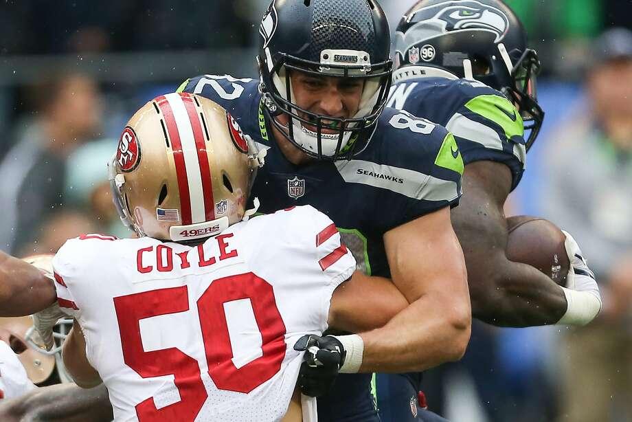Seahawks corner back Justin Coleman blocks 49ers linebacker Brock Coyle from running back Chris Carson in the first half at CenturyLink Field on Sunday, Sept. 17, 2017. (GRANT HINDSLEY, seattlepi.com) Photo: GRANT HINDSLEY, SEATTLEPI.COM