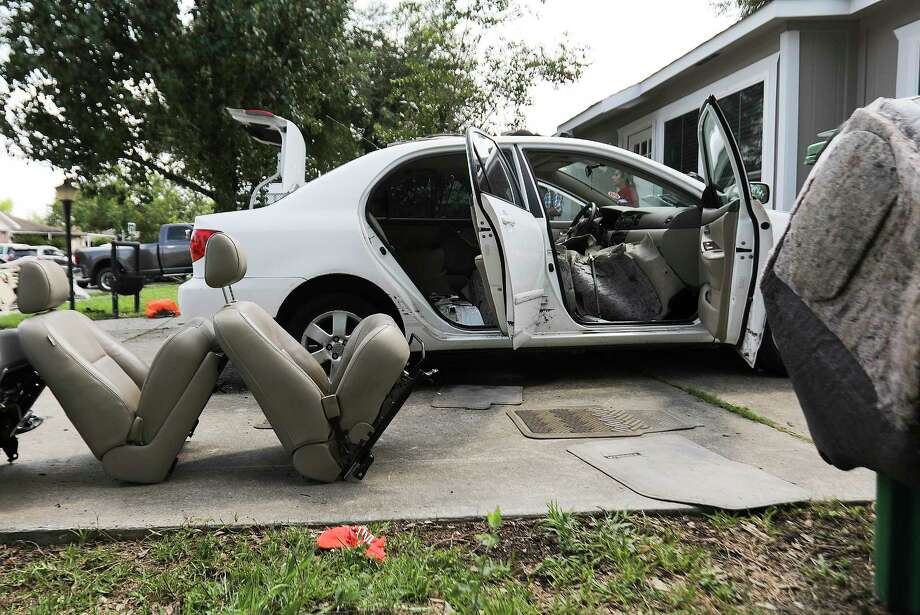 Christina Rodriguez dries out her car in her driveway after it took in water from Tropical Storm Harvey on  Friday, Sept. 1, 2017, in Houston. ( Elizabeth Conley / Houston Chronicle ) Photo: Elizabeth Conley, Staff / © 2017 Houston Chronicle