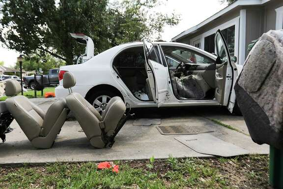 Christina Rodriguez dries out her car in her driveway after it took in water from Tropical Storm Harvey on  Friday, Sept. 1, 2017, in Houston. ( Elizabeth Conley / Houston Chronicle )