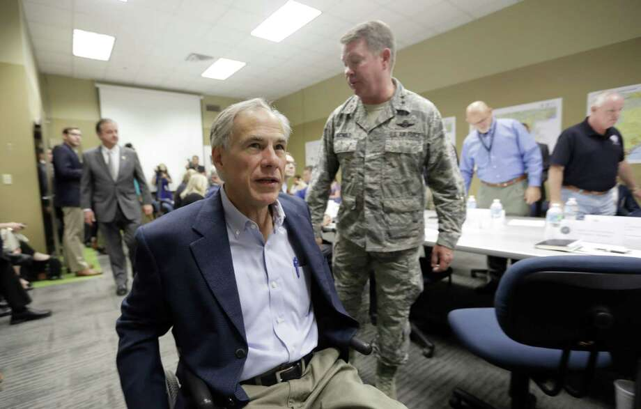 Texas Gov. Greg Abbott, left, passes Maj. Gen. John F. Nichols, right, as he and Commissioner John Sharp, rear, arrive last month for a briefing on Hurricane Harvey recovery efforts at the new FEMA Joint Field Office in Austin. The office will hire 300 Texans during a job fair Saturday and Sunday in Austin. Photo: Eric Gay /Associated Press / Copyright 2017 The Associated Press. All rights reserved.