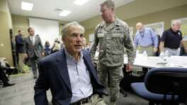 Texas Gov. Greg Abbott, left, passes Maj. Gen. John F. Nichols, right, as he and Commissioner John Sharp, rear, arrive last month for a briefing on Hurricane Harvey recovery efforts at the new FEMA Joint Field Office in Austin. The office will hire 300 Texans during a job fair Saturday and Sunday in Austin.