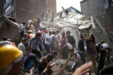 People remove debris from a collapsed building following an earthquake in the neighborhood of Condesa, Mexico City, Mexico, on Tuesday, Sept. 19, 2017. A powerful 7.2 magnitude earthquake struck near Mexico City, toppling buildings and extinguishing lights as thousands of people fled. It was the nation's second major earthquake this month, and struck 32 years to the day after a temblor with an 8.0 magnitude killed 5,000 people.