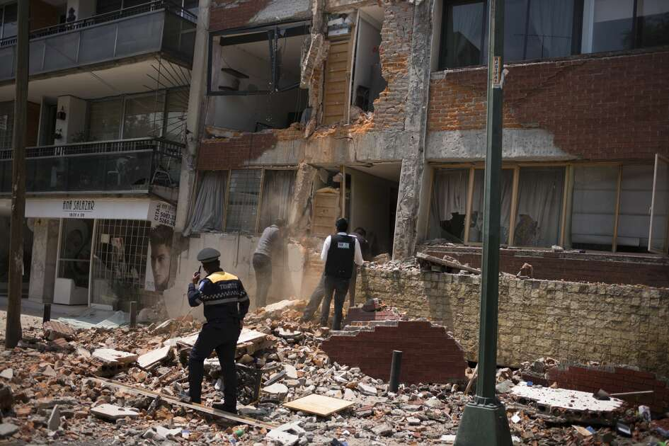 Rescue officials search a collapsed building following an earthquake in the neighborhood of Condesa, Mexico City, Mexico, on Tuesday, Sept. 19, 2017. A powerful 7.2 magnitude earthquake struck near Mexico City, toppling buildings and extinguishing lights as thousands of people fled. It was the nation's second major earthquake this month, and struck 32 years to the day after a temblor with an 8.0 magnitude killed 5,000 people.