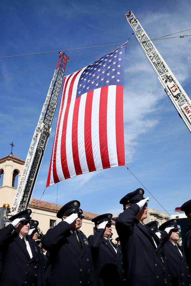 Firefighters salute as Terry Smerdel's casket is carried into St. Ignatius Parish for his funeral. Photo: Santiago Mejia, The Chronicle