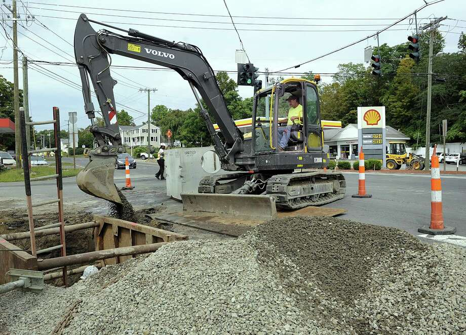 Workers relocate a catch basin at the interesction of the four corners in Brookfield, Thursday, Sept. 14, 2017. This is part of the Streetscape project and creation of the Brookfield Town Center. Photo: Carol Kaliff / Hearst Connecticut Media / The News-Times