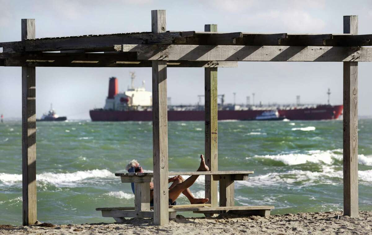 A man rests with his feet up on a picnic table as a fully laden oil tanker leaves Port Corpus Christi. The Port and the U.S. Army Corps. of Engineers are working together to compelted a $327 million widening and deepening of the Corpus Christi Ship Channel.