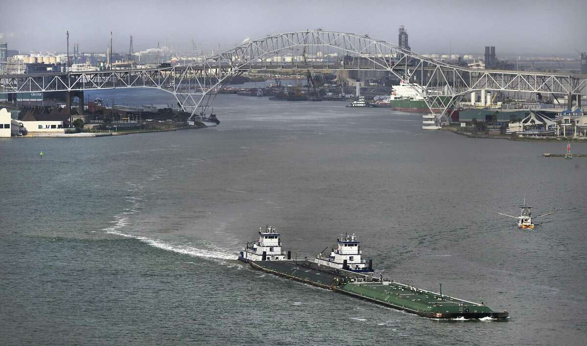 """Tugs push an oil barge out of Port Corpus Christi. Part of the expansion of the main ship channel will be """"barge shelves"""" that will allow barges to move alongside the main channel and improve safety."""