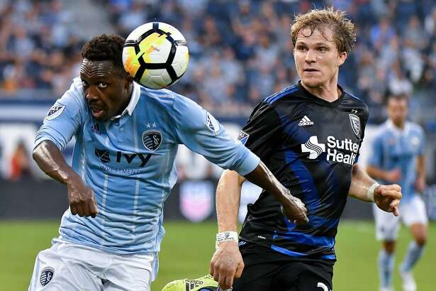 In this Aug. 9, 2017 photo, Sporting KC forward Gerso Fernandes directs the ball past San Jose Earthquakes midfielder Florian Jungwirth in the first half of U.S. Open Cup semifinals soccer game in Kansas City, Kansas.   Fernandes was born in Bissau, Guinea-Bissau and raised in two different orphanages in Portugal, before finding his way into professional soccer. In his first season in the United States, Fernandes leads Sporting KC with nine goals across all competitions. (John Sleezer/The Kansas City Star via AP)
