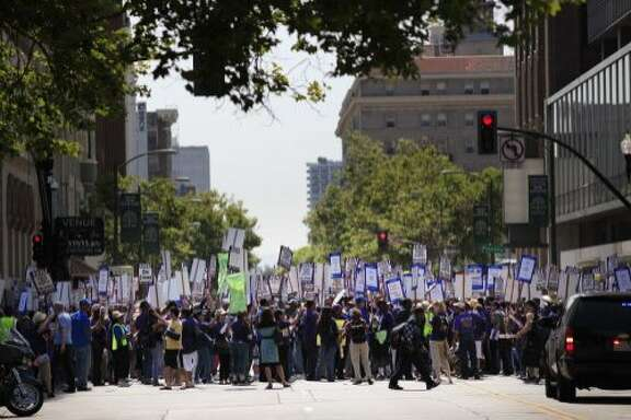 Blocking the street to traffic, SEIU 1021 union members comprised of BART and City of Oakland workers on strike today at Frank Ogawa Plaza on Monday July 1, 2013 in Oakland, Calif. Workers say they are protesting unfair labor practices and demand greater investment in critical public services.