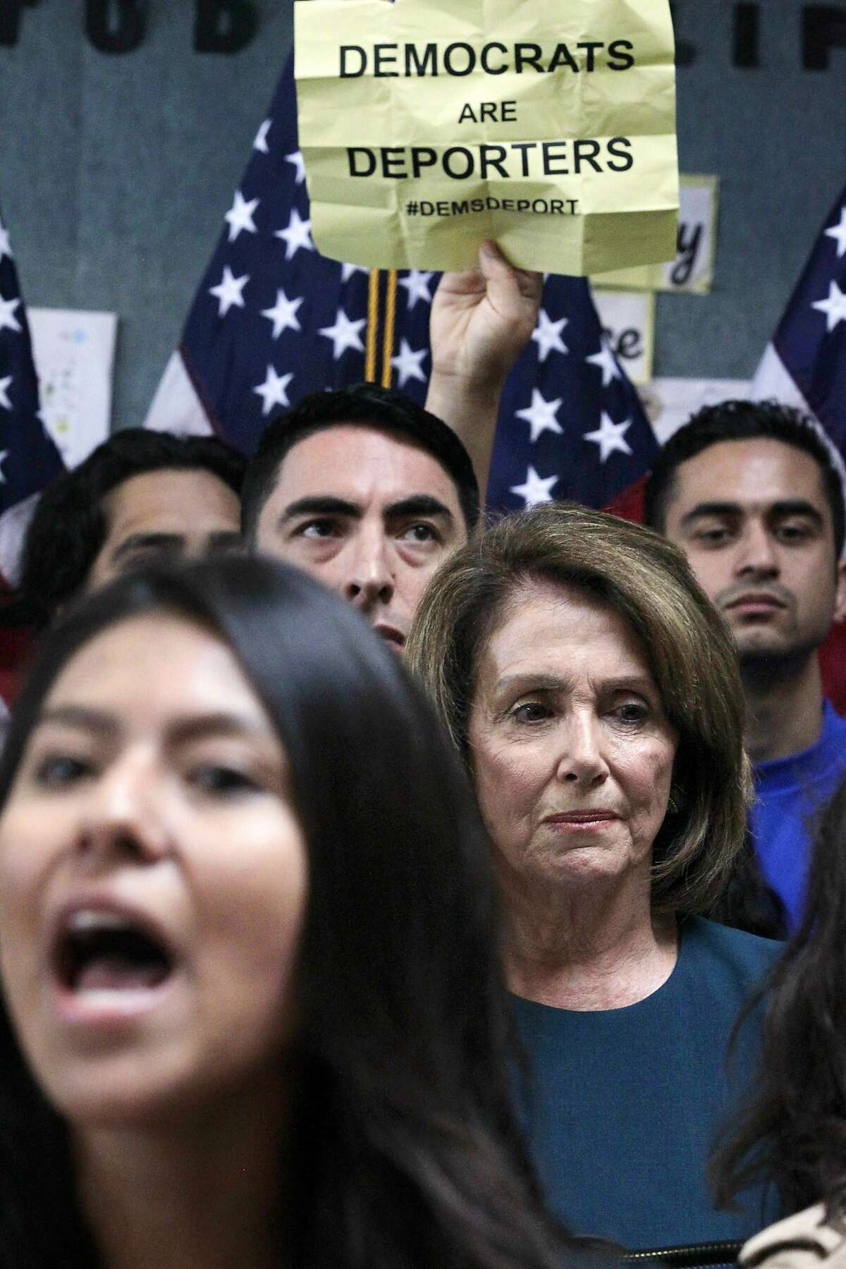 U.S. Rep. Nancy Pelosi, D-Calif., waits as protesters yell during a press conference on the Deferred Action for Childhood Arrivals, or DACA program, on Monday, Sept. 18, 2017 in San Francisco. Several dozen young immigrants shouted down Pelosi, the top Democrat in the U.S. House, on Monday during an event in San Francisco, following her recent conversations with President Donald Trump over the future of a program that grants many of them legal status. (Lea Suzuki/San Francisco Chronicle via AP)
