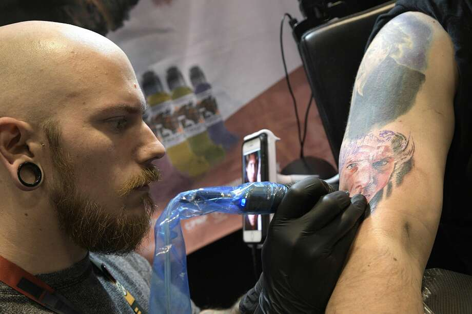 Artist Pony Lawson, left, of Chicago, works on a tattoo of Hans Solo for Jason Stone, of Tampa, Fla., during the Star Wars Celebration event Friday, April 14, 2017 in Orlando, Fla. (Phelan M. Ebenhack/Chicago Tribune/TNS) Photo: Phelan M. Ebenhack/TNS