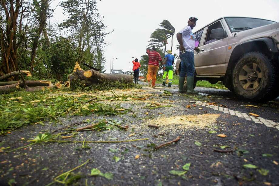 Rescuers clear an uprooted tree from a road in the village of Viard Petit-Bourg on Tuesday in the French territory of Guadeloupe after Hurricane Maria had passed. Photo: CEDRICK ISHAM CALVADOS, Contributor / AFP or licensors
