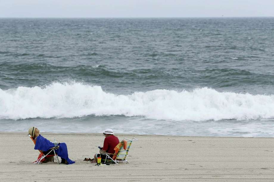 A couple sits on chairs as waves crash on the beach at Seaside Heights, N.J.,, Thursday. Swells are up from recent hurricanes in the Atlantic Ocean, including Hurricane Jose, which is expected to stay out to sea, according to meteorologists. Photo: Julio Cortez — The Associated Press  / Copyright 2017 The Associated Press. All rights reserved.
