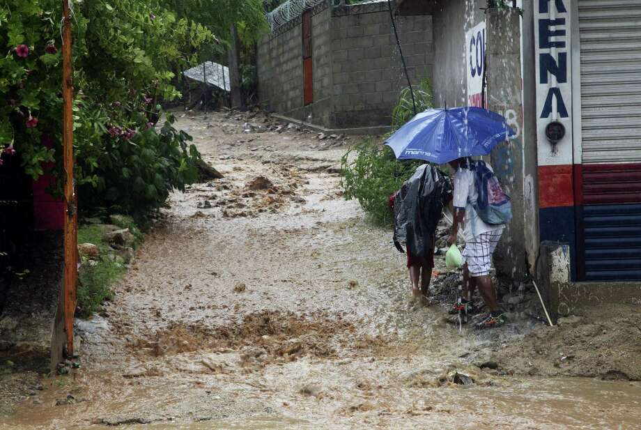 People walk under a downpour on a flooded street in Acapulco, Guerrero state, Mexico onSept. 14, 2017. Hurricane Max hit Mexico's southern Pacific coast as a Category 1 storm Thursday and was expected to move inland into Guerrero state, a region that includes the resort city of Acapulco. Photo: AP Photo — Bernandino Hernandez  / Copyright 2017 The Associated Press. All rights reserved.
