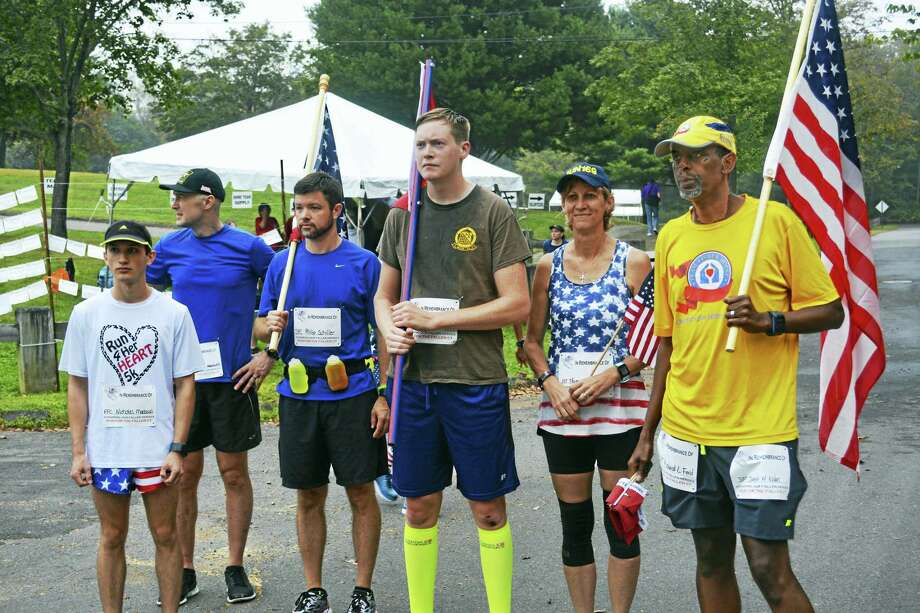 The 9 a.m. group, led by pacer Adam Osmond, far right, ready themselves for their 8K lap at the Run for the Fallen CT at Veterans Memorial Park in Middletown Saturday morning. A total of 64M, or 40 miles, was run. Photo: Cassandra Day / Hearst Connecticut Media