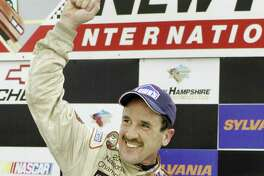 In this Sept. 16, 2005 photo, Ted Christopher celebrates his victory in the Busch North Series Sylvania 125 at the New Hampshire International Speedway in Loudon, N.H. NASCAR officials say modified championship racer Christopher was one of two people killed when a small plane crashed in Connecticut. The Federal Aviation Administration confirms that two people were aboard a Mooney M20C plane that went down in a wooded area near the North Branford-Guilford border shortly before 2 p.m. Saturday, Sept. 16, 2017. NASCAR says Christopher and the plane's pilot died.