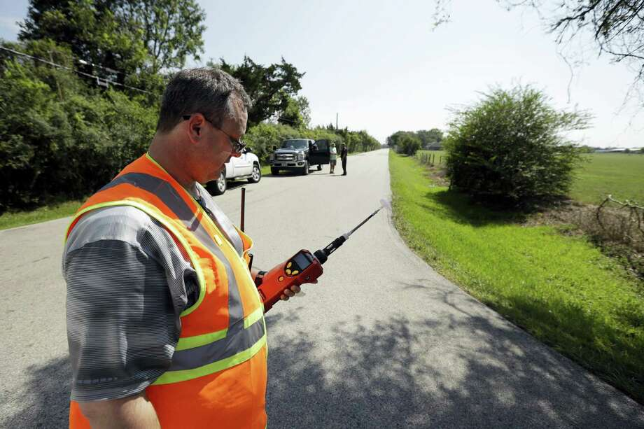 Mike Cossey, of Bureau Veritas, uses an air monitor to check the quality of air at a police roadblock marking the 1.5-mile perimeter of the evacuation area around the Arkema Inc. chemical plant Thursday, Aug. 31, 2017, in Crosby, Texas. The Houston-area chemical plant that lost power after Harvey engulfed the area in extensive floods was rocked by multiple explosions early Thursday, the plant's operator said. The Arkema Inc. plant had been left without refrigeration for chemicals that become volatile as the temperature rises. Photo: Gregory Bull / AP Photo  / Copyright 2017 The Associated Press. All rights reserved.