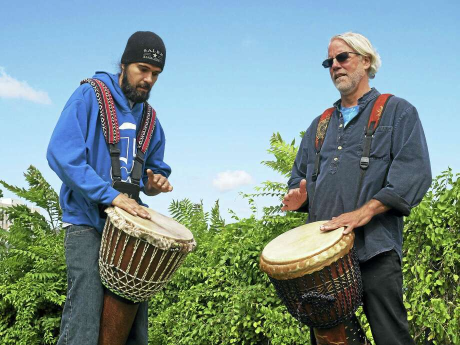 Drummers Andrew Mark Prue of East Granby and Craig Norton of Middletown play djembes at Harbor Park on the Connecticut River Wednesday morning. Photo: Cassandra Day — Hearst Connecticut Media