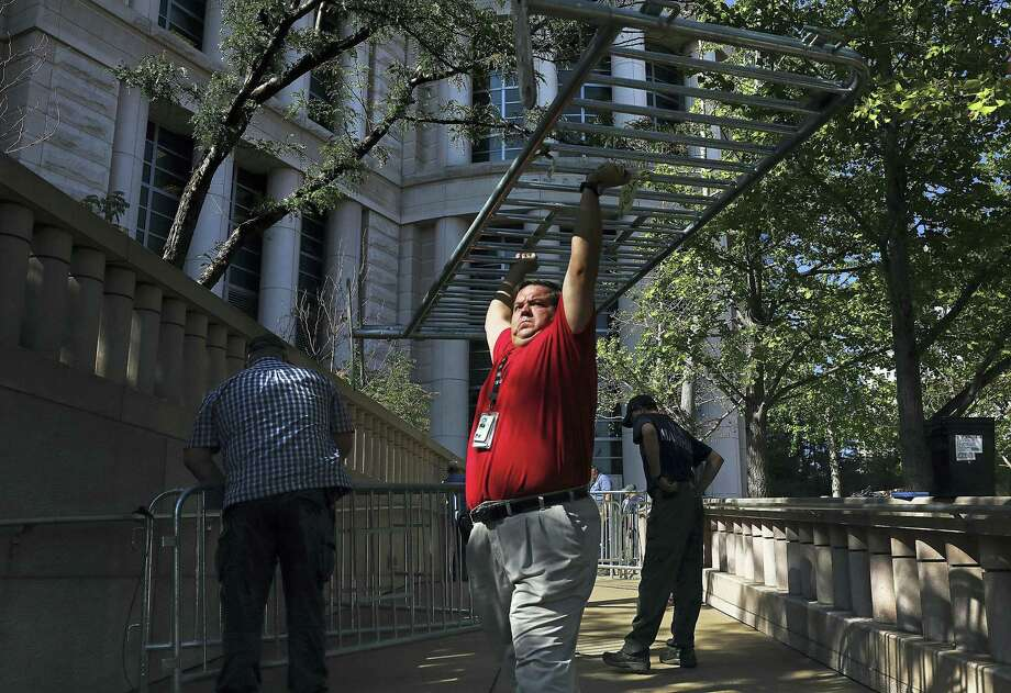 Officials begin erecting barricades outside the Thomas F. Eagleton federal courthouse in St. Louis on Thursday, Sept. 14, 2017, before an expected verdict in the trial of former St. Louis Police officer Jason Stockley. St. Louis police officers will begin working 12-hour shifts starting Friday in anticipation of a ruling in the trial. Stockley fatally shot 24-year-old Anthony Lamar Smith in December 2011. Stockley testified Smith was reaching for a gun in his car. Prosecutors say Stockley planted the gun. Photo: Christian Gooden/St. Louis Post-Dispatch Via AP   / St. Louis Post-Dispatch