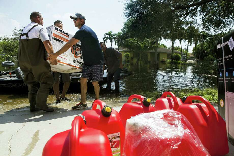 In this Thursday, Sept. 14, 2017, photo, Louis Sarangi, from left, Walter Crespo, and Jason Dolle carry a generator to Sarangi's home along athe flooded Quinn Street area in Bonita Springs, Fla., in the aftermath of Hurricane Irma. Photo: Nicole Raucheisen/Naples Daily News Via AP   / 2017 Naples Daily News
