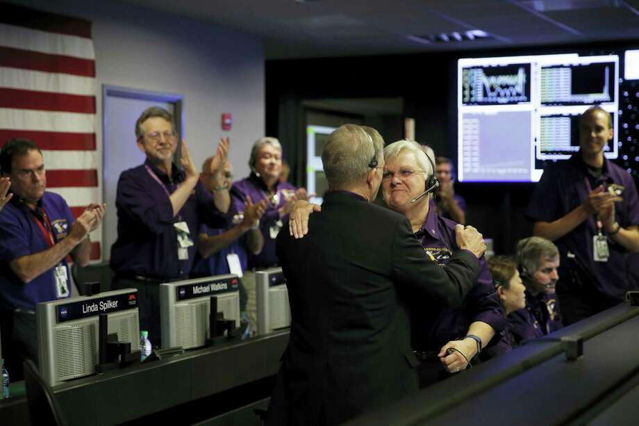 Project manager Earl Maize, center left, and flight director Julie Webster hug in mission control at NASA's Jet Propulsion Laboratory, Friday, Sept. 15, 2017, in Pasadena, Calif., after confirmation of Cassini's demise. Cassini disintegrated in the skies above Saturn early Friday, following a remarkable journey of 20 years. Photo: AP Photo/Jae C. Hong, Pool   / Copyright 2017 The Associated Press. All rights reserved.