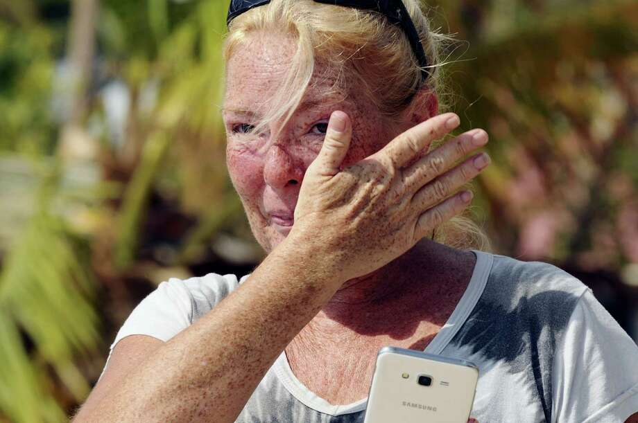 Dixie Crystal Mathews, 47, cries as she watches workers from Robbie's Restaurant and Marina raise the American flag Wednesday, Sept. 14, 2017,  at the end of the damaged docks at the popular restaurant and marina in Islamorada, Fla. Photo: Taimy Alvarez/South Florida Sun-Sentinel Via AP   / Sun Sentinel 2017