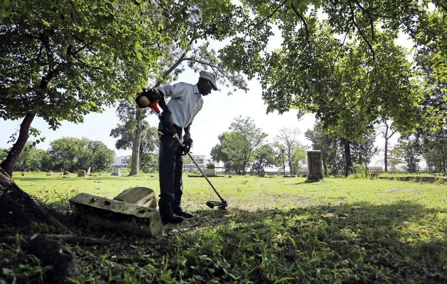 In this Sunday, Sept. 10, 2017, photo Charles Cook, groundskeeper at Olivewood Cemetery, trims grass at the cemetery in Houston. Hurricane Harvey floodwaters exposed dozens of caskets at swamped cemeteries in Texas and Louisiana last month, the grim result of shallow graves set in spongy soil, and a scene that may reappear as Florida cleans up after Hurricane Irma. Photo: Louis DeLuca/The Dallas Morning News Via AP   / The Dallas Morning News