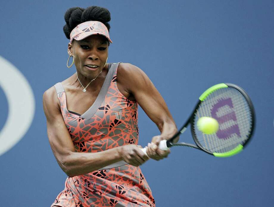 Venus Williams returns a shot from Viktoria Kuzmova during the first round of the U.S. Open tennis tournament Monday. Williams won in three sets. Photo: SETH WENIG — THE ASSOCIATED PRESS  / Copyright 2017 The Associated Press. All rights reserved.