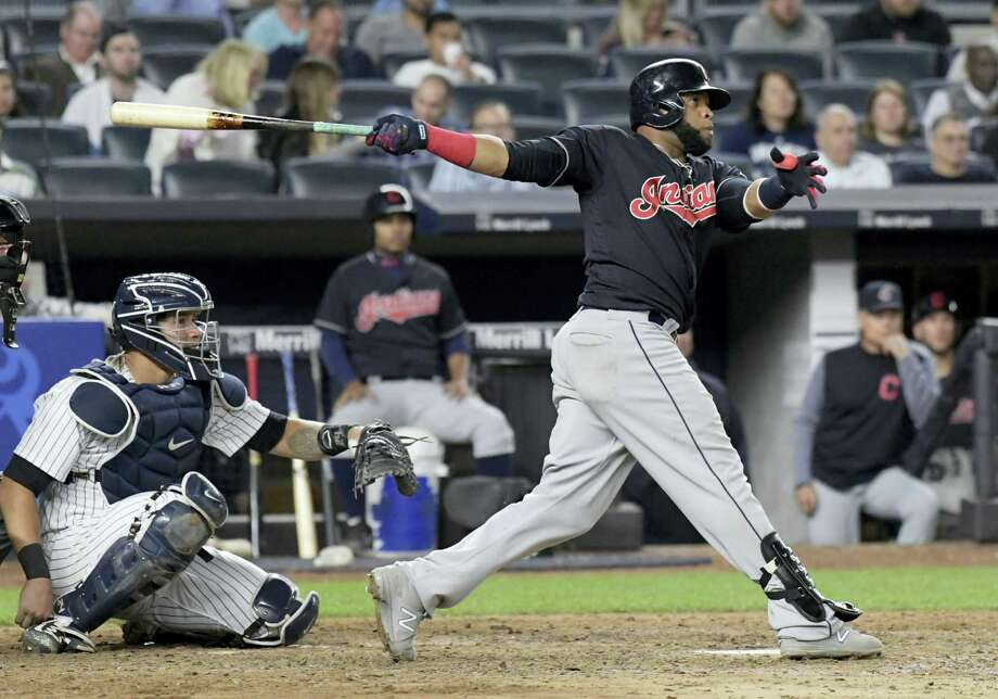 Cleveland Indians' Carlos Santana hits a home run as New York Yankees catcher Gary Sanchez, left, looks on during the seventh inning Monday at Yankee Stadium. The Indians prevailed 6-2. Photo: Bill Kostroun — The Associated Press  / FR51951 AP
