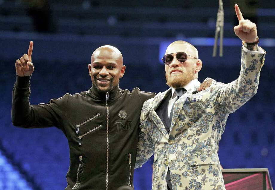 Floyd Mayweather Jr., left, and Conor McGregor pose during a news conference after a super welterweight boxing match Aug. 27, 2017 in Las Vegas. Photo: AP Photo — Isaac Brekken  / FR159466 AP